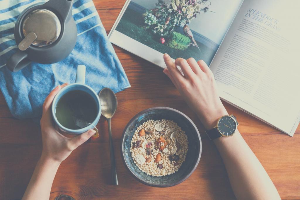 Schreibtisch mit gesundem Frühstück, Tee und Zeitschrift